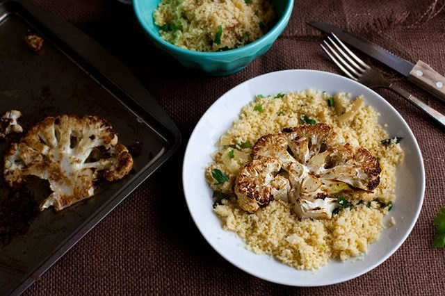 Roasted and browned cauliflower steaks on a bed of caramelized onion couscous.