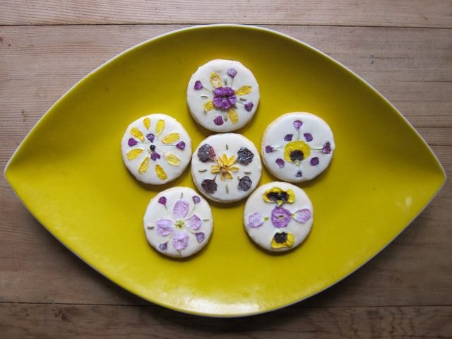 A plate of frosted sugar cookies decorated with edible flowers.