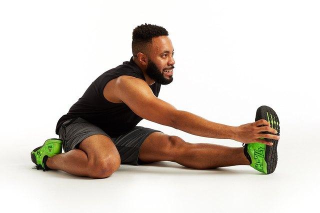 man doing a leg stretch against a white backdrop