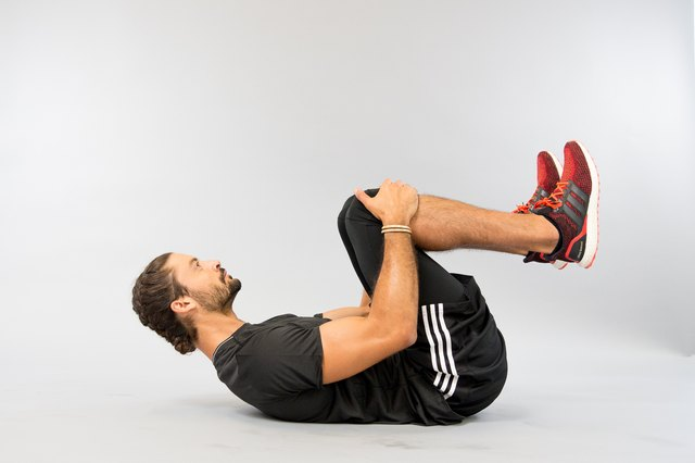 Man performing seated roll exercise.