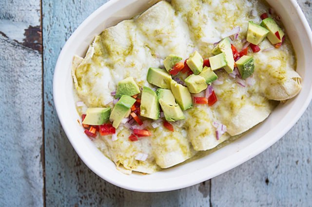 A casserole dish of enchiladas topped with diced peppers and avocados.