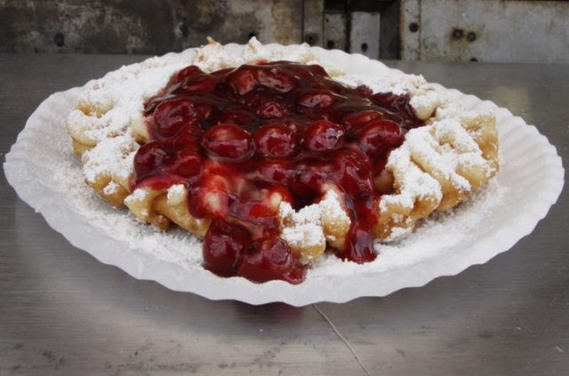 Golden funnel cake drizzled with powdered sugar and fresh strawberries.
