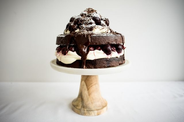 A two-layered black forest cake with a poached cherry and cream filling.