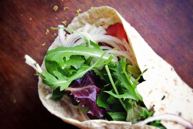 Close view of a wrap with hummus and vegetables on a wooden table