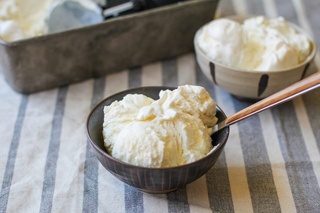 Two bowls of vanilla ice cream on a stripped table cloth
