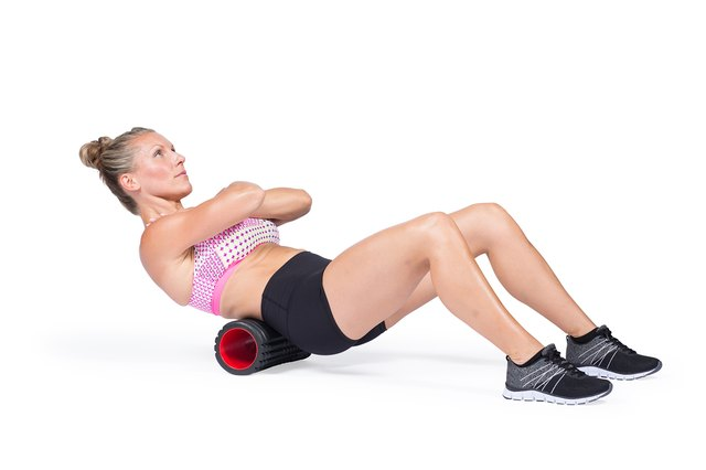 Athlete massaging upper back muscles with foam roller.