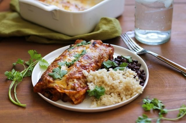 A plate of vegetarian enchiladas, black beans and brown rice.