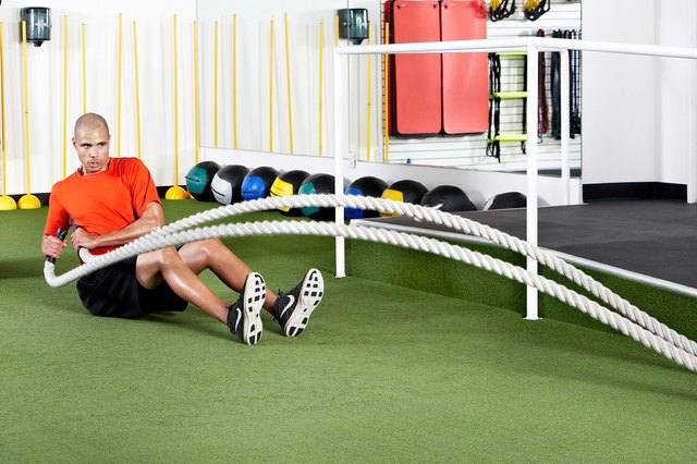 Man doing seated hip-toss rotations with the battle ropes
