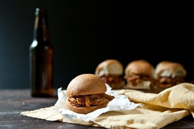 Multiple chipotle beer chicken sliders served with a bottle of brew.