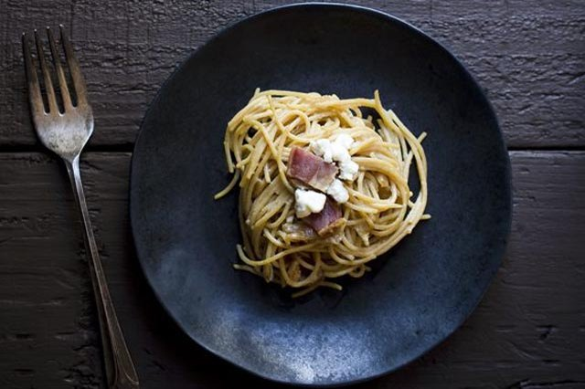 A plate of spaghetti sprinkled with caramelized onions, bacon and goat cheese.