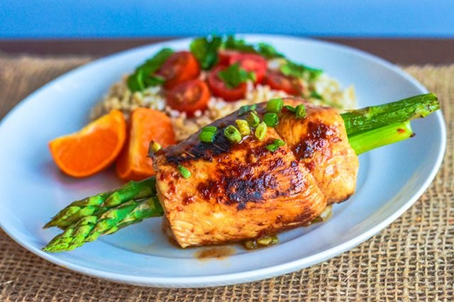 Sweet and spicy teriyaki chicken-wrapped asparagus served with rice, cherry tomatoes and orange slices.