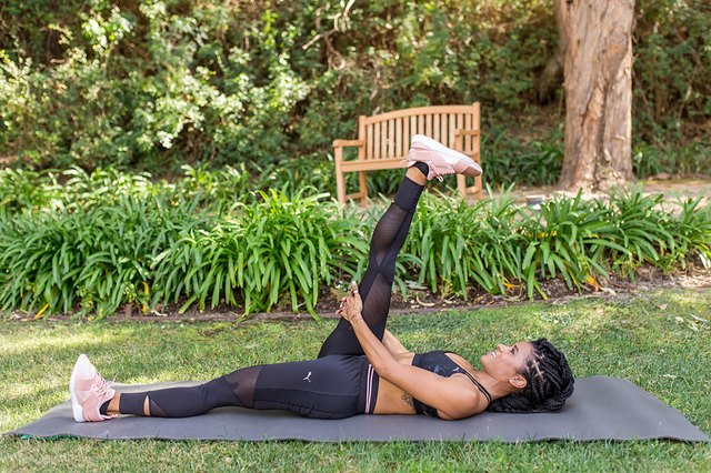 woman doing supine hamstring stretch on a yoga mat outside