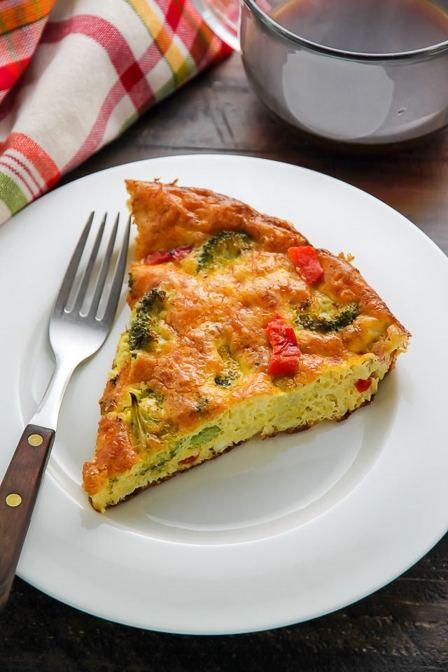 A large slice of broccoli frittata on a white plate