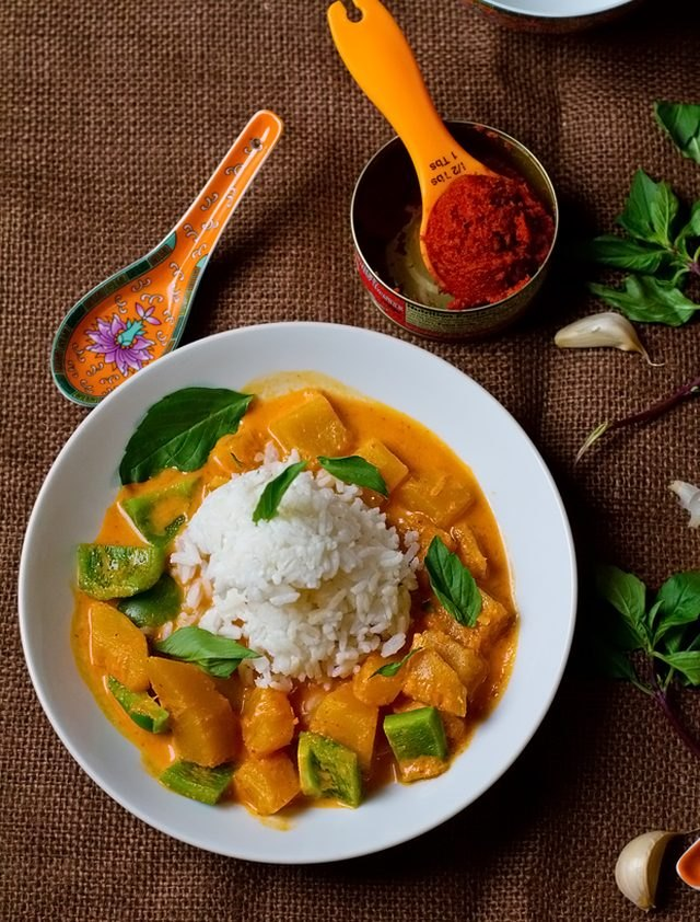 Thai pumpkin curry with green bell peppers and fresh basil leaves, and a scoop of steamed rice.