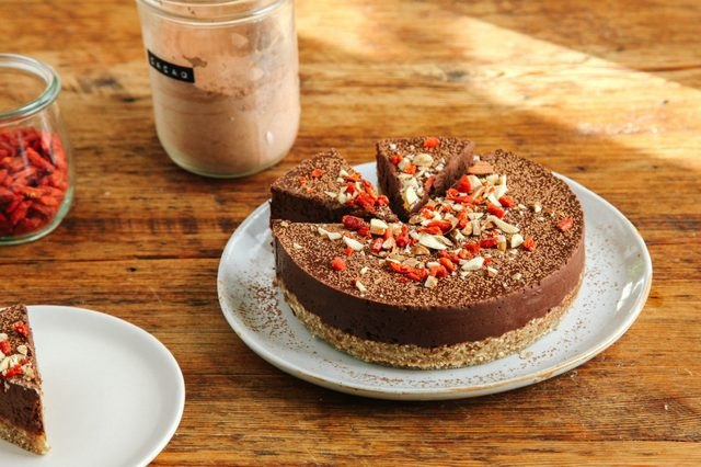 A sliced chocolate and almond tart sprinkled with almond slices and goji berries.