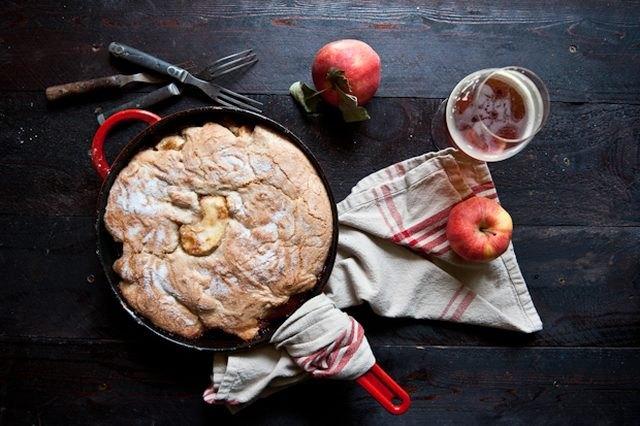 A cast iron cobbler next to a glass of hard apple cider