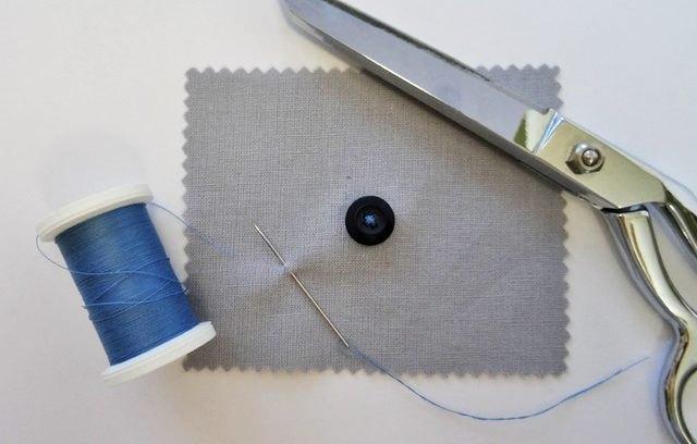 Button, thread and scissors.