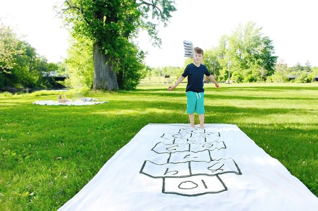 white canvas hopscotch court and a child getting ready to hop