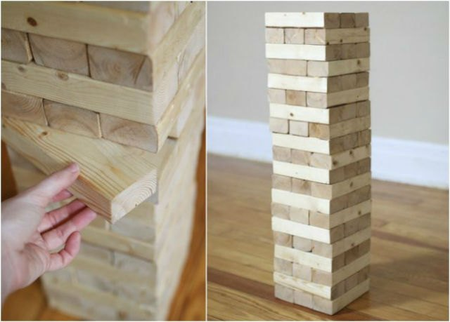 A hand removing a jenga piece from giant jenga tower on left, jenga tower standing on wooden floor on right