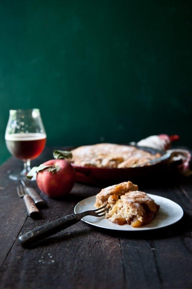 A warm slice of hard apple cider skillet cobbler served with a glass of hard cider.