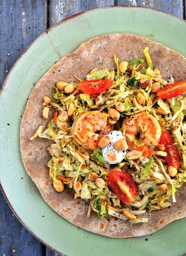 Plate with shrimp fajitas and honey-roasted peanuts on a tortilla.