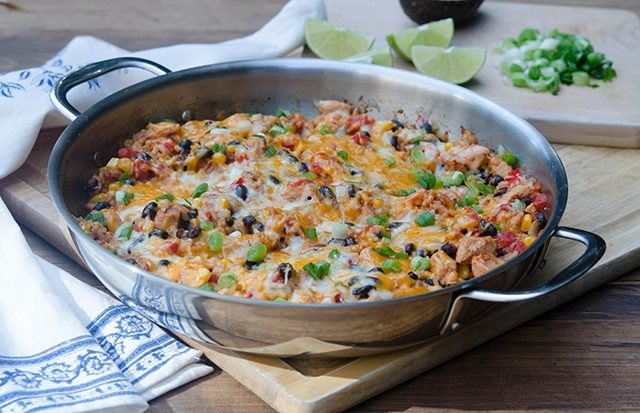 Tex-Mex chicken and rice skillet served with lime wedges and cilantro