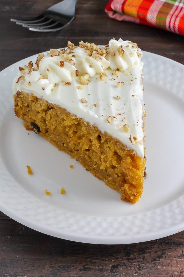 A spongy, orange pumpkin cake topped with cream cheese frosting and sprinkled with nuts.