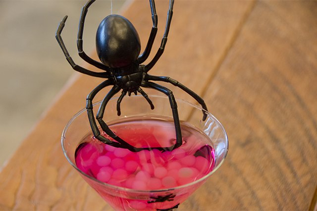 Martini glass filled with a raspberry lemon drop and boba as spider eggs.