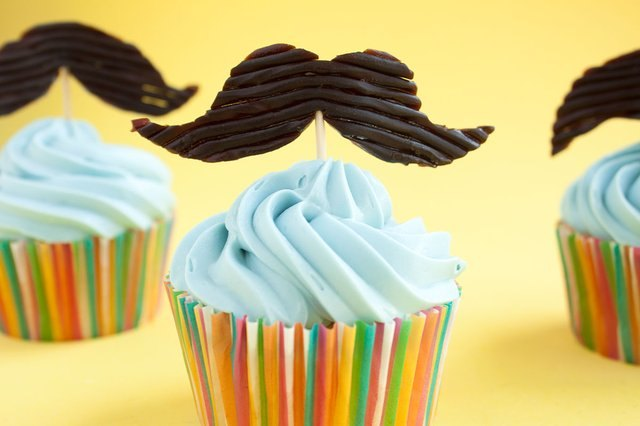 cupcakes with blue frosting and mustache toppers
