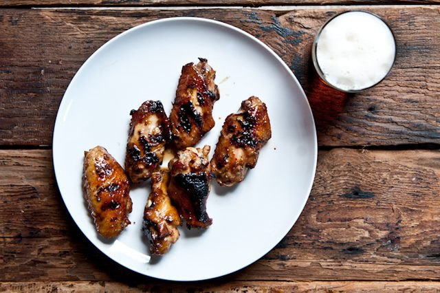 A plate of five honey glazed wings served with a glass of beer.