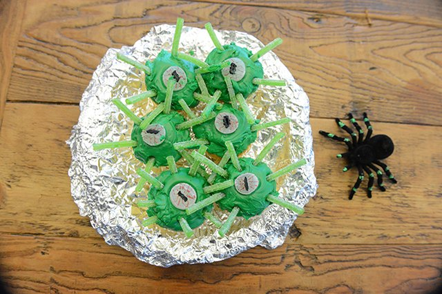 Green cupcakes decorated to look like alien eyes.