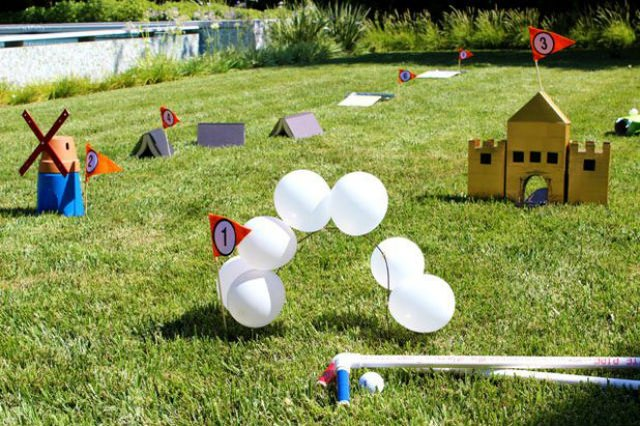 Homemade mini golf course with a ballon arch, small castle, flowerpot windmill on a lawn