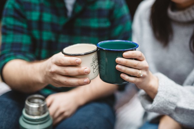 A couple shares a thermos of coffee.