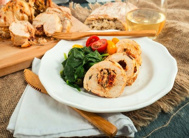 Plate of stuffed chicken breast with side salad.