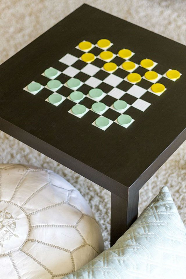 Black table painted with a checkerboard and green and yellow checker pieces