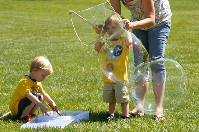 One child dipping bubble wand in soap, another blowing bubbles with the help of a woman