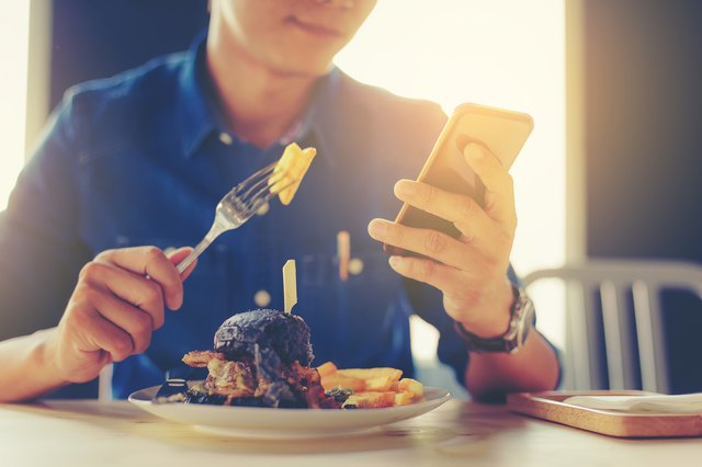 man on smartphone while eating a burger