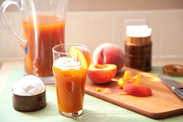 Glass and pitcher of peach tea.