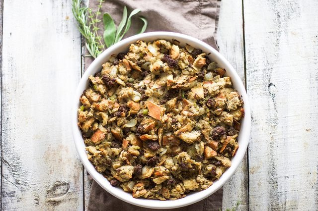 A round dish full of stuffing on a wooden table