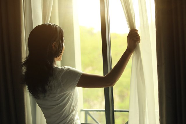 Woman opening curtains to wake up before exercise.