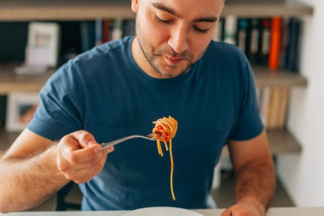 Young man eating spaghetti bolognese