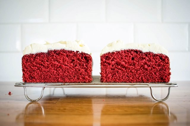 Slices of red velvet pound cake topped with white frosting.
