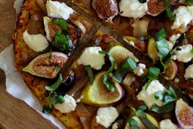 A cauliflower-crusted pizza topped with basil, figs and cheese.
