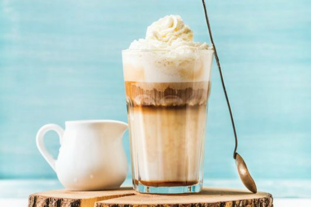 Latte macchiato with whipped cream, serving silver spoon and pitcher