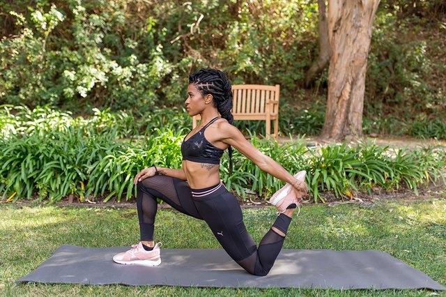 woman doing kneeling quad stretch on yoga mat outside
