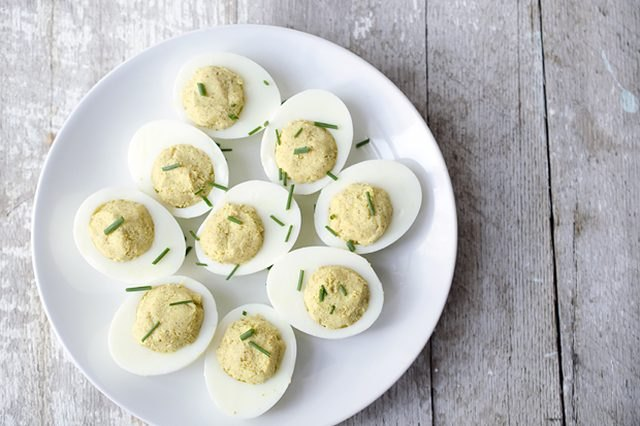 A platter of curried deviled eggs sprinkled with chives.