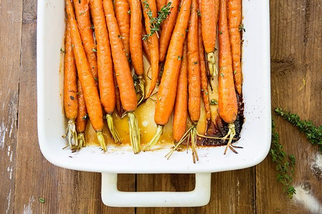 A white casserole dish with roasted honey-rum glazed carrots