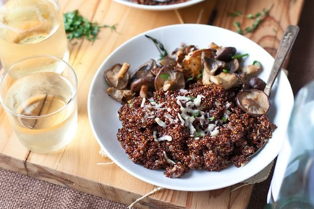 A bowl of wild mushroom quinoa risotto served with wine.