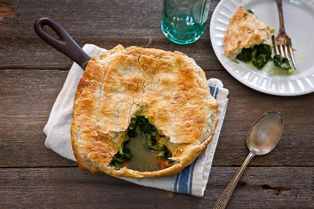 A large skillet spinach and artichoke pot pie on a wooden table