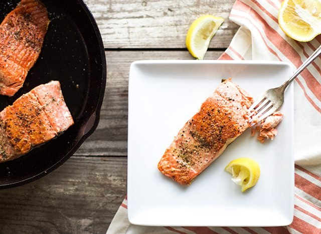 Seared salmon served with lemon wedges